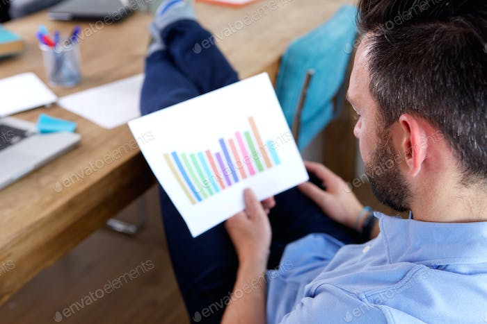 Business man analyzing growing charts at his desk
