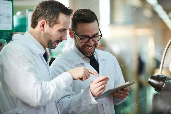 Two Factory Workers Wearing Lab Coats