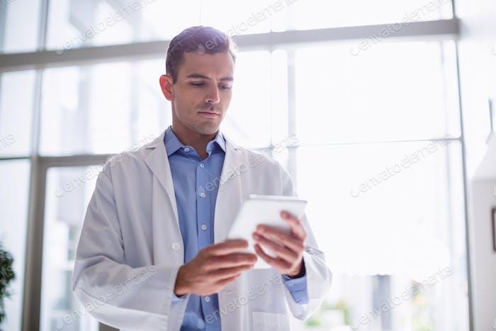 Doctor using digital tablet in corridor