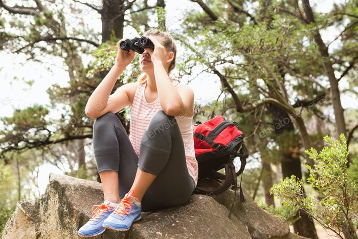 Blonde hiker sitting on rock and  looking through binoculars in the nature