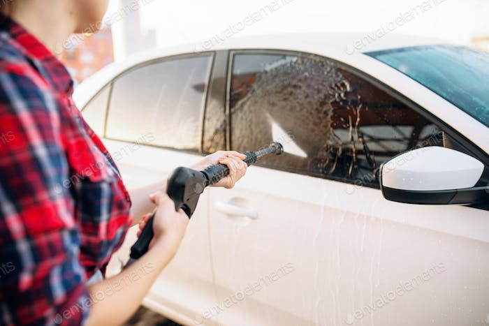 Female person wash off the foam from the car glass