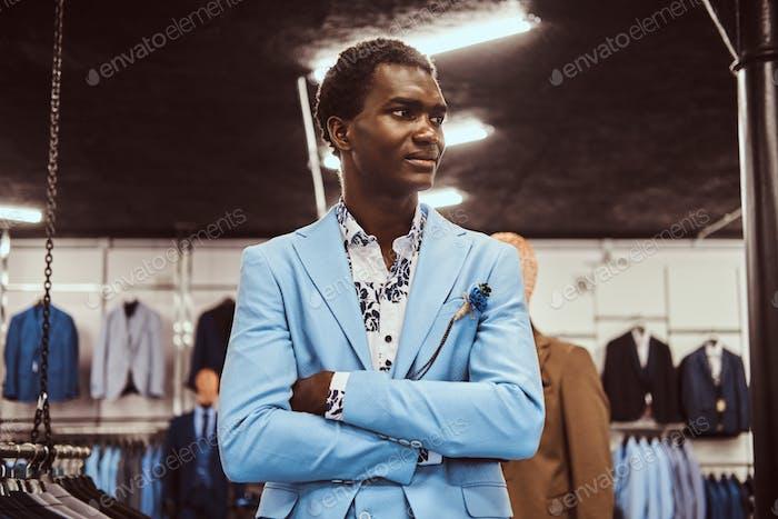 Афро-американский мужчина, одетый в синий элегантный костюм позирует в классическом магазине мужской одежды