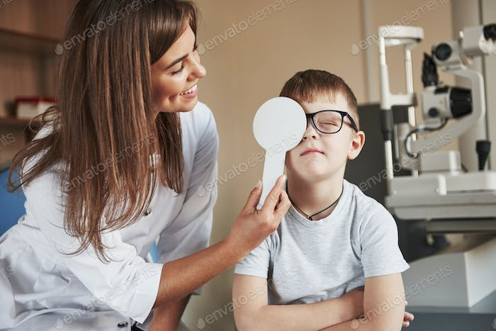 Sight test in clinic. Female doctor covers kid eye with medical tool for checking visual acuity