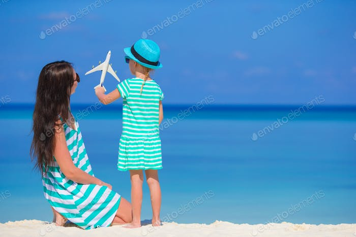 Young woman and little girl with miniature of airplane at beach