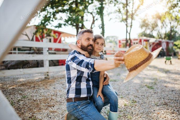 Ein Vater mit kleiner Tochter im Freien auf Familienfarm, im Gespräch