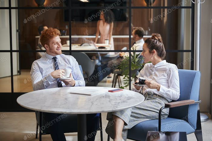 Male and female colleagues talk over coffee at office cafe