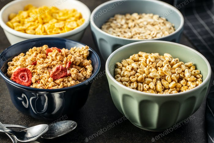 Verschiedene Frühstückscerealien in Schüsseln. Puffweizen und Haferflocken.