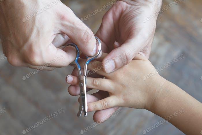 Vater schneiden die Nägel seiner Tochter