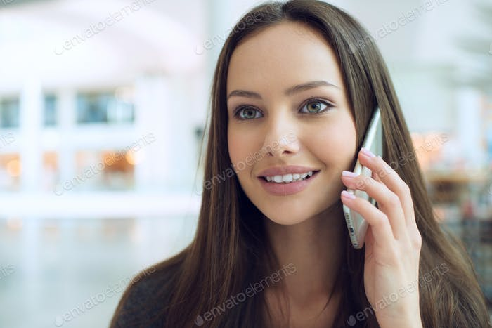 Happy young  woman speaking by cellphone indoor.