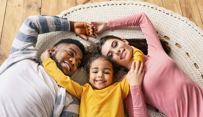 Smiling multiracial family lie on the floor