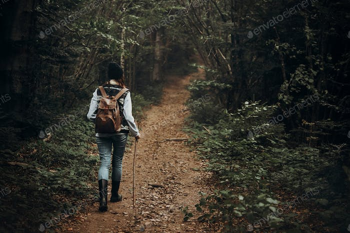 hipster traveler with backpack walking in woods. stylish woman hiking
