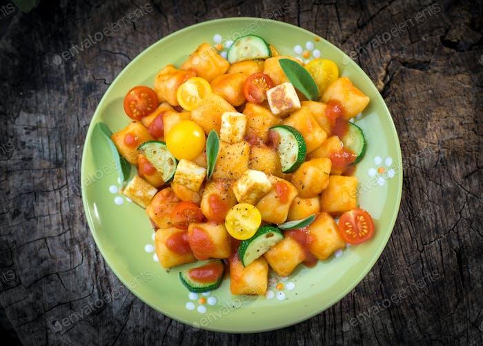 Homemade Italian gnocchi with tomato sauce and zucchini