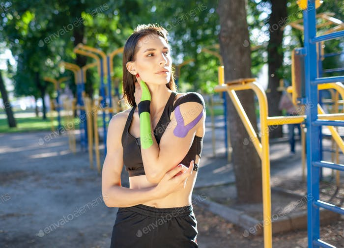 Sports woman with kinesiological taping posing outdoors