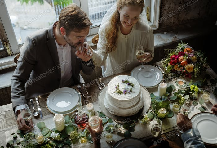 Groom Kissing Bride Hand on Wedding Reception