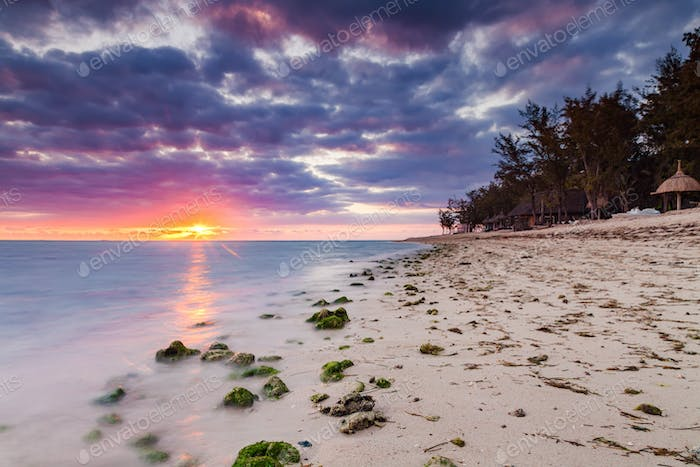 Beautiful sunset on the beach in a tropical resort at Reunion island.