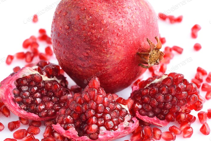 Pomegranate fruit with seeds on white background