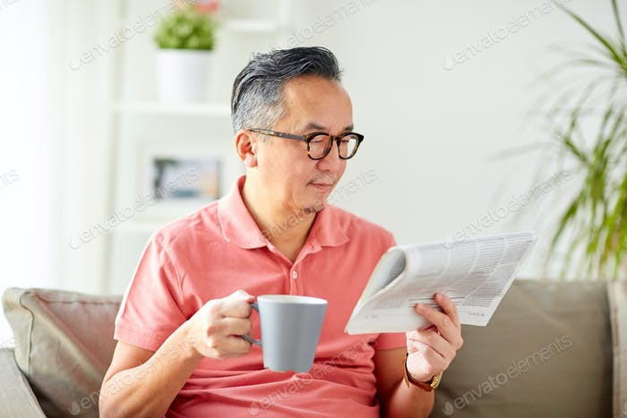 man drinking coffee and reading newspaper at home