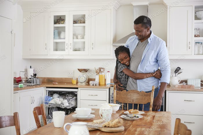 Daughter Helping Father To Clear Table After Family Meal