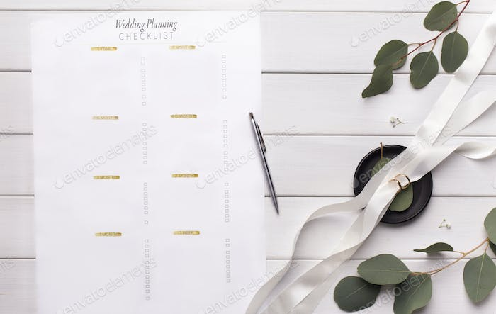 Wedding planning checklist with items on white wood