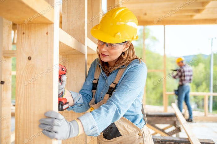 Female worker at construction site during work with wood frame house