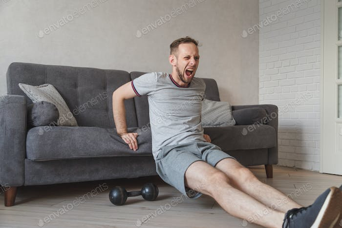 Young caucasian guy working out at home with sofa