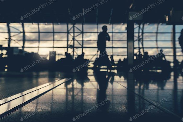 Entfokussierte Silhouetten von Geschäftsleuten, die auf dem Flughafen reisen.