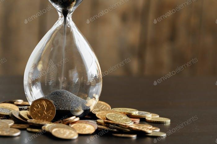 El tiempo es dinero. Cierre de reloj de arena con monedas de dinero