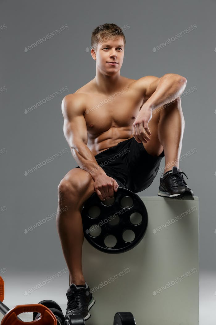 Shirtless muscular guy sits on white box.
