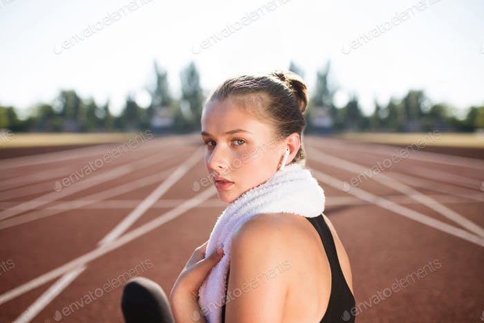 Beautiful girl in wireless earphones with towel on neck thoughtfully looking in camera on racetrack