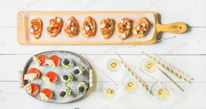 Brushettas, gazpacho shots, desserts, champagne and straws over white background