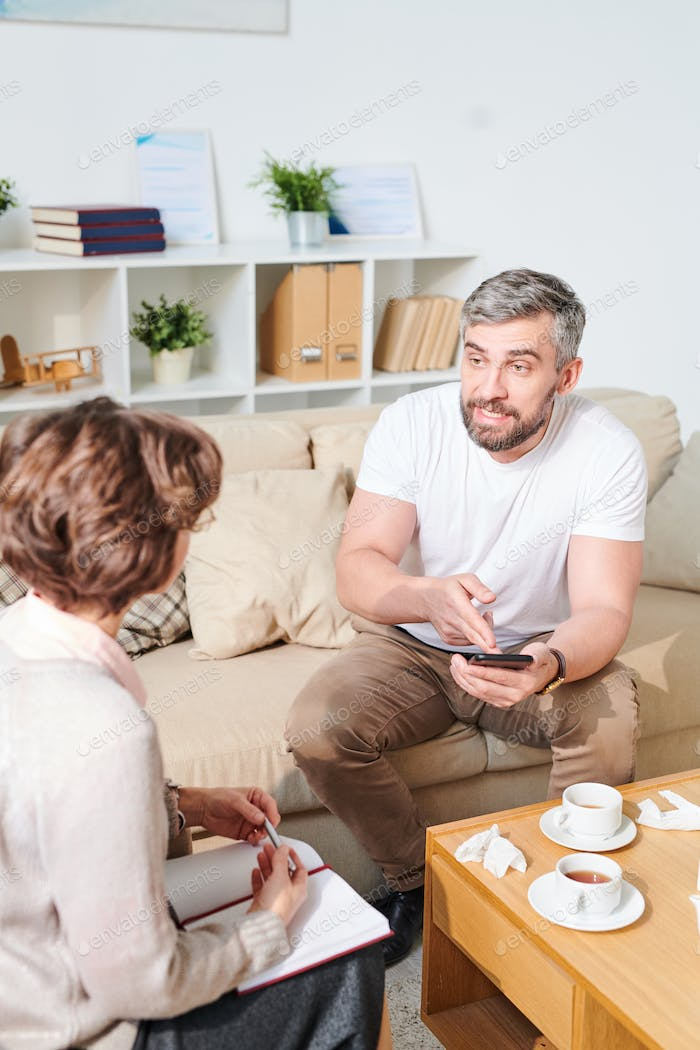 Annoyed man sharing his problems with psychiatrist