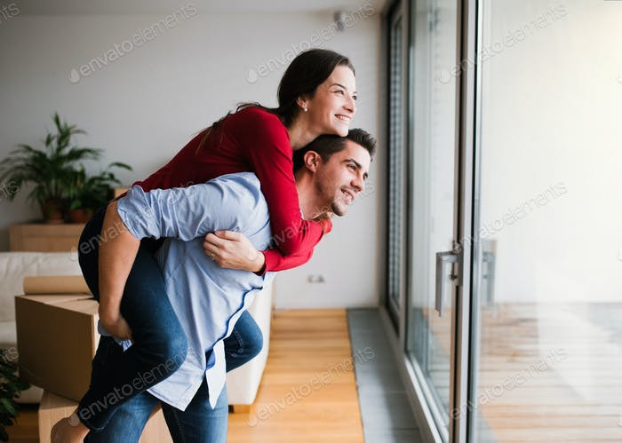Young couple moving in a new home, having fun.