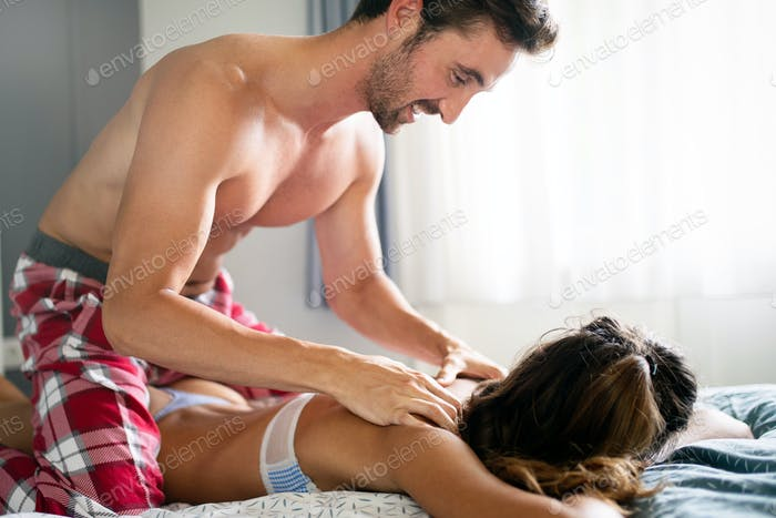 Cheerful young couple making massage at home
