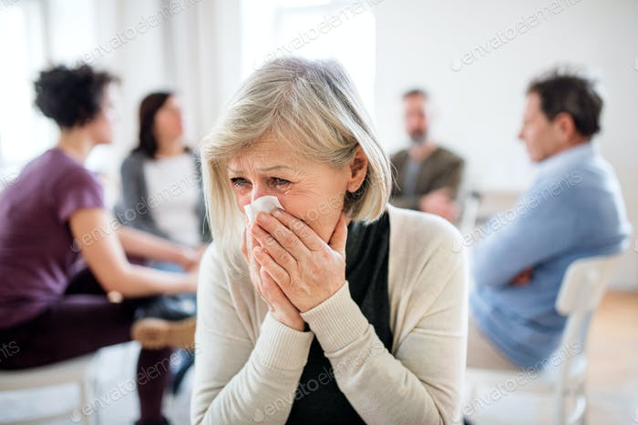 A portrait of senior depressed woman crying during group therapy.