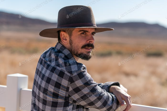Cowboy with grey hat, moustache and checker shirt