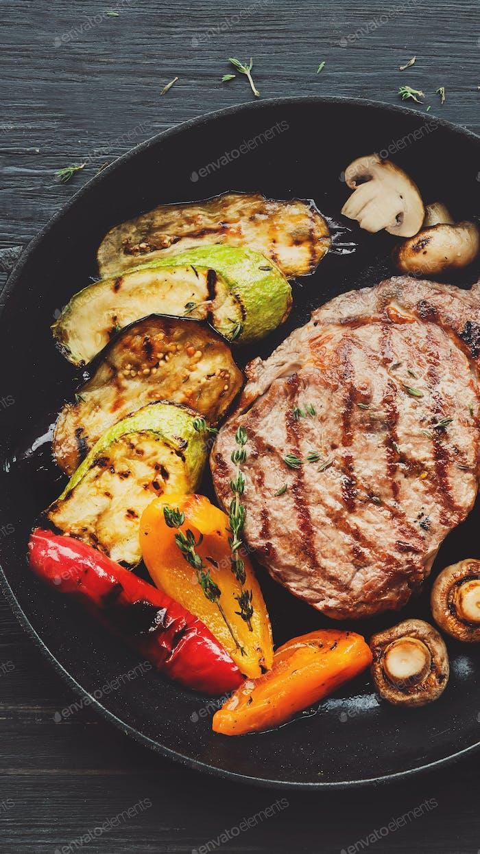 Gegrilltes Rindfleischsteak und gebratenes Gemüse auf dunklem Holztisch