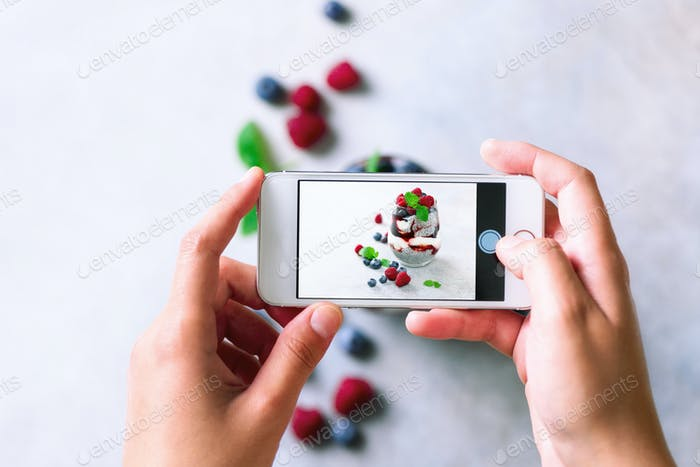 Girl is taking photos of breakfast, chia pudding with berries to mobile phone. Social media