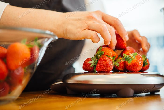 Woman putting strawberry on scales