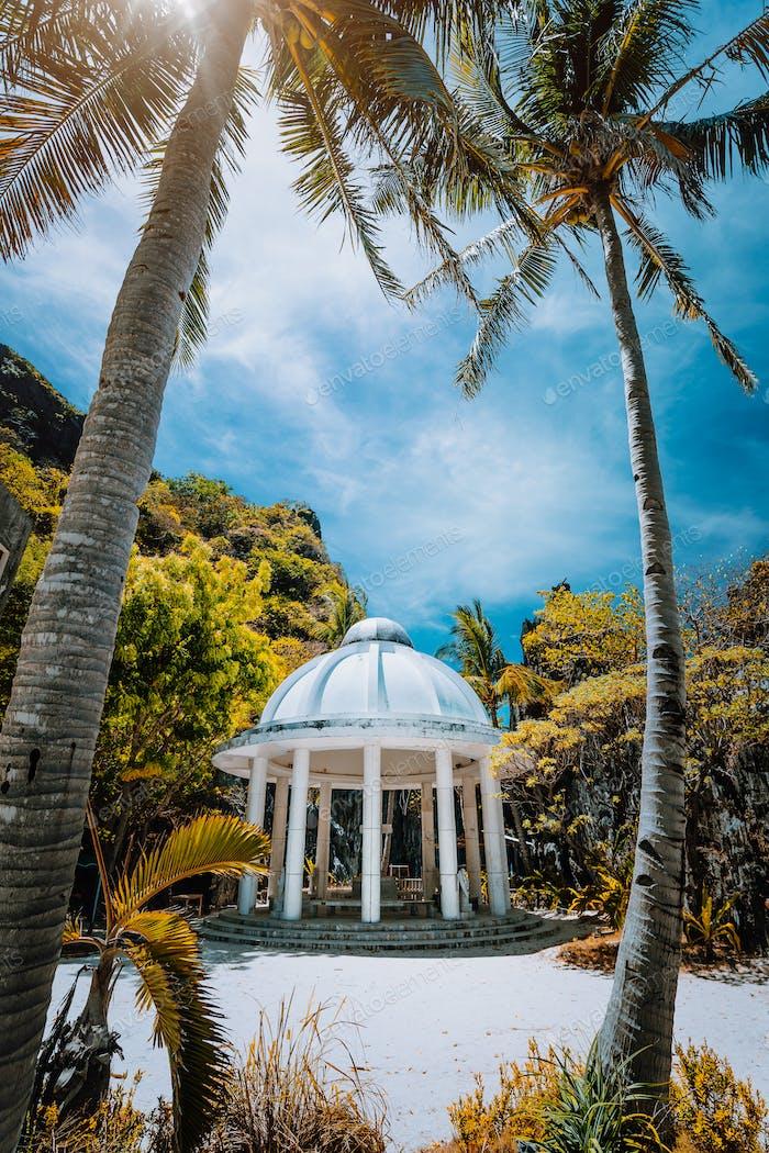 Verlassener Matinloc Schrein zwischen zwei Palmen an der Westküste der Insel Matinloc in Palawan