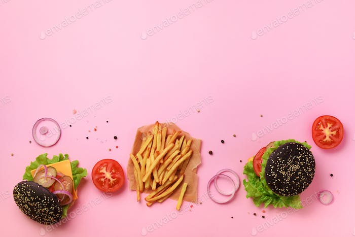 Black burger, french fries potatoes, tomatoes, cheese, onion, cucumber and lettuce on pink