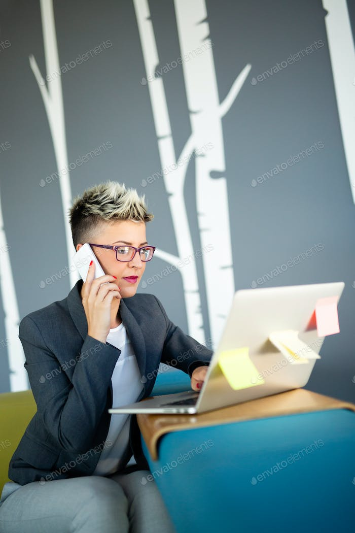 Portrait of successful businesswoman working with laptop