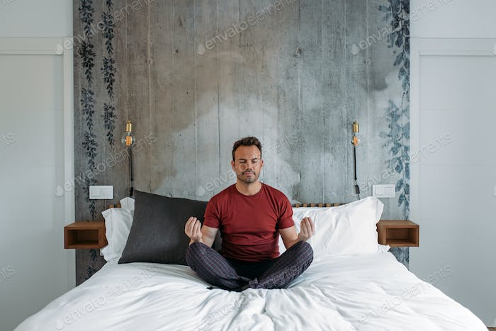 Attractive man on bed meditating