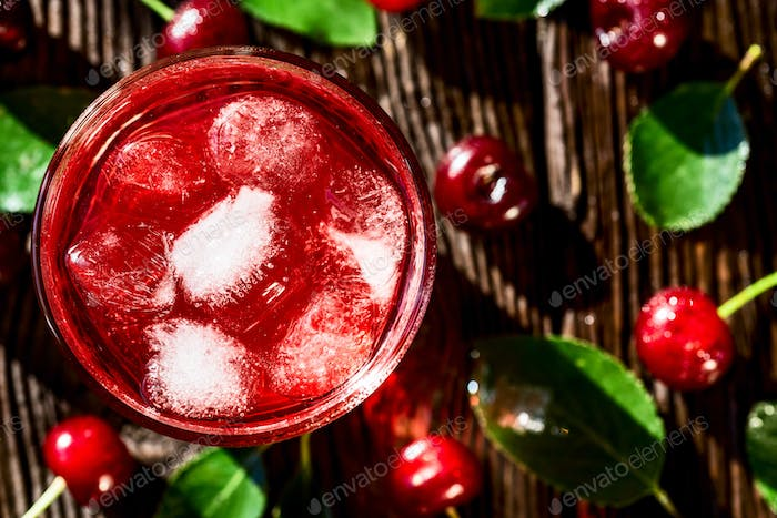 Top view cherries and cherry fruit drink on wood