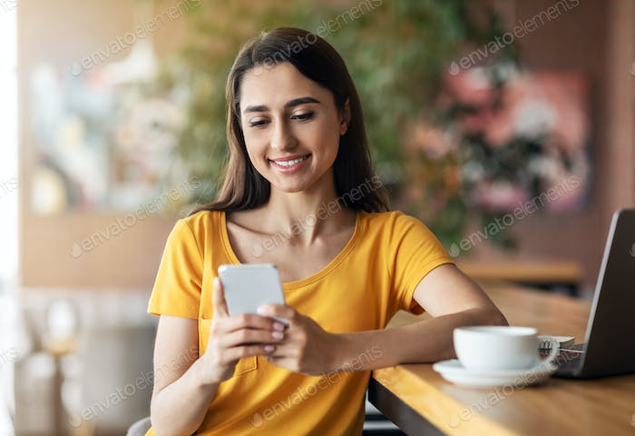 Happy girl sitting at cafe, drinking tea and using smartphone