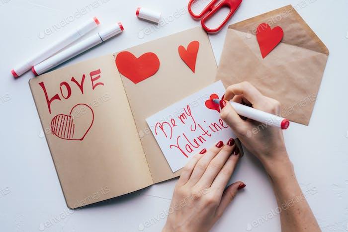 Frau hält Filzstift in der Hand und malt romantische Valentinstagskarte mit roter Farbe.