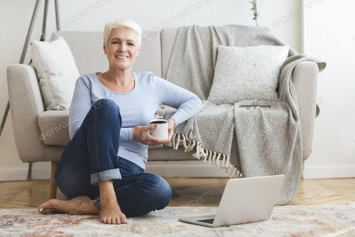 Aged business lady enjoying cup of tea at home