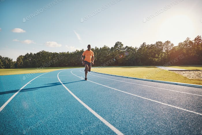 Fit young athlete sprinting alone down an outdoor track