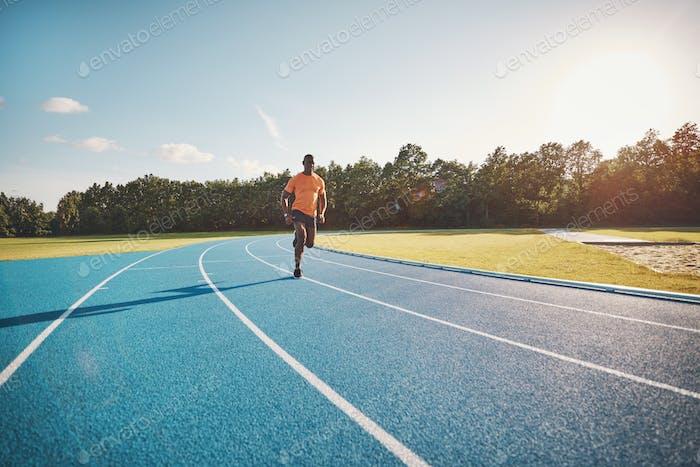 Fit junge Sportler Sprinting allein auf einer Outdoor-Strecke