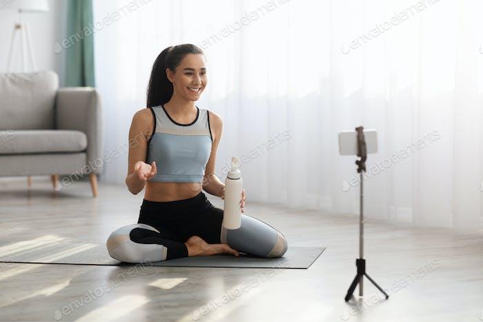 Junge Frau Fitnesstrainerin, die von zu Hause aus sendet