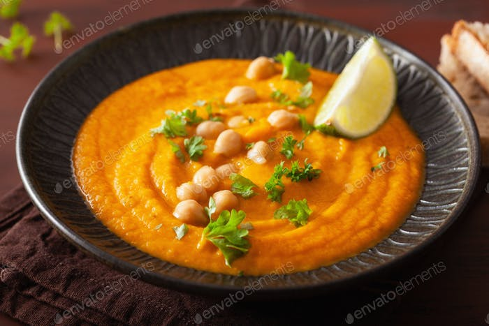 creamy carrot chickpea soup on dark rustic background